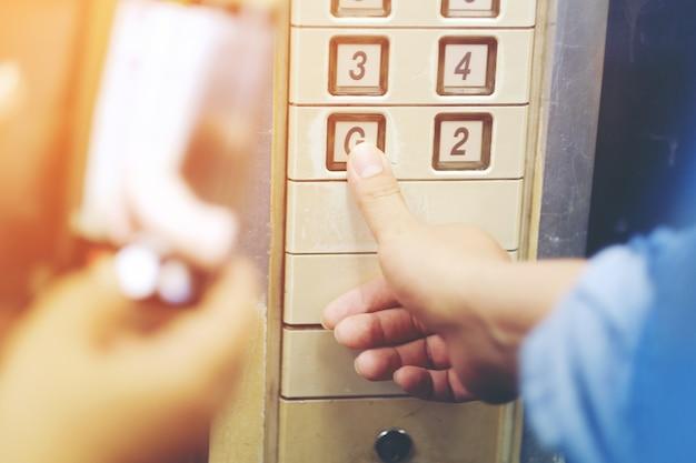 De hand drukt op de oude liftknop