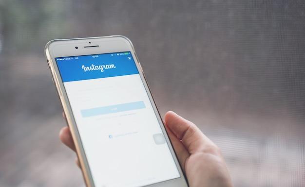 De hand drukt op het instagram-pictogram van het login-scherm