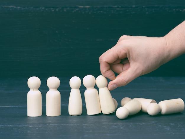 De hand duwt de houten figuren van mannen, ze vallen in verschillende richtingen