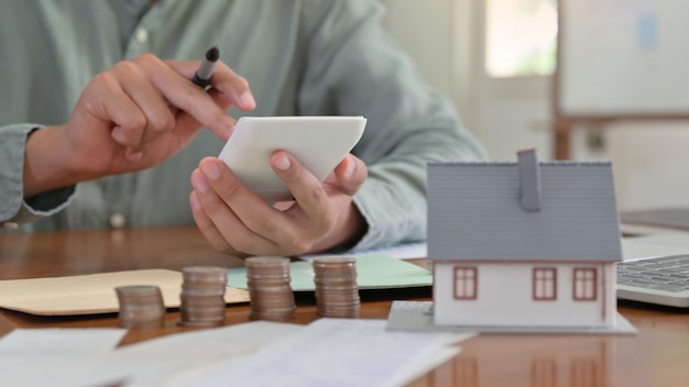 De hand gebruikt calculator om de huisuitgaven te berekenen.