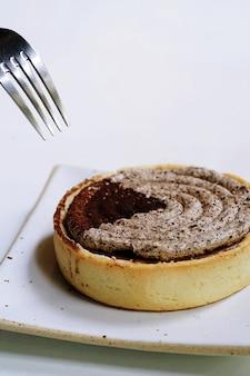 De hand gebruikt vork een italiaans dessert, rond gemaakte tiramisu scherp geplaatst op witte plaat, tirami