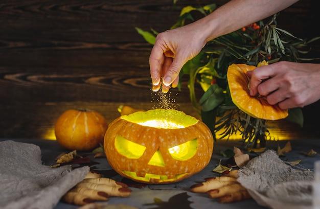 De hand giet gloeiend poeder in een pompoen met een gesneden gezicht