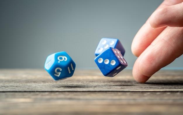 De hand gooit blauwe dobbelstenen op de houten tafel. het concept van een casino en een gelukkige kans om te winnen