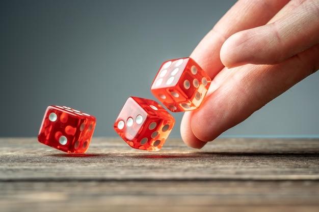De hand gooit rode dobbelstenen op de houten tafel. het concept van een casino en een gelukkige kans om te winnen