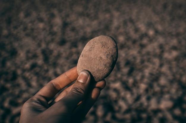 De hand hield een steen vast en er was veel steen op de achtergrond.