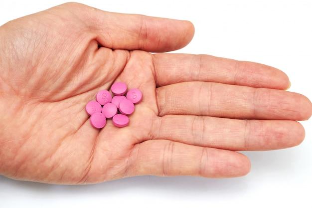 De hand hield medische pillen vóór mondeling neem in het medische concept van de gezondheidszorgconsumptie