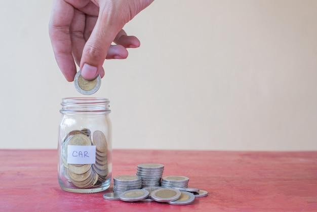 De hand houden munt en zetten spaarmunten in glas met een stapel munten op rode houten tafel. werkplek met kopie ruimte - investering, business, finance en banking concept