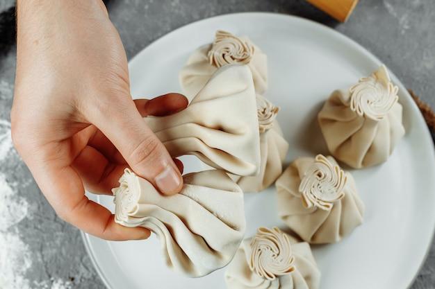 De hand houdt de chikali bij de staart vast. khinkali in een georgisch restaurant in de hand. georgische keuken.
