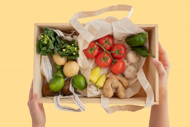 De hand houdt de doos van het pijnboomhout en de katoenen netto zak met verse groentenvlakte lag op gele achtergrond. plastic vrij voor boodschappen boodschappen en bezorging. levensstijl zonder afval