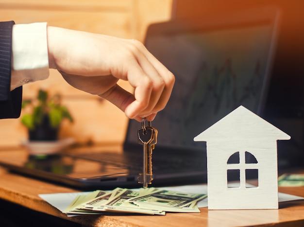 De hand houdt de sleutels van het huis vast. concept van onroerend goed. verkoop of verhuur van woningen