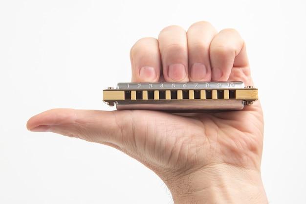 De hand houdt een mondharmonica op een witte achtergrond. klassiek muzikaal blaasinstrument