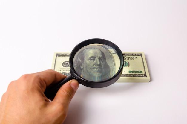 De hand houdt een vergrootglas vast en kijkt naar een rekening van honderd dollar.