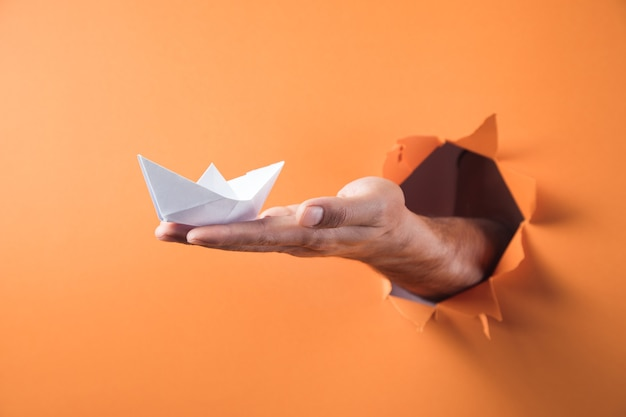 De hand houdt een witboekboot op een oranje achtergrond