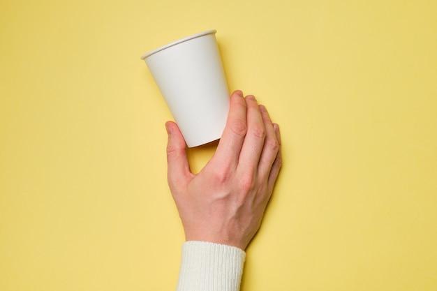 De hand houdt een witte kartonnen beker op een gele achtergrond. bespotten.