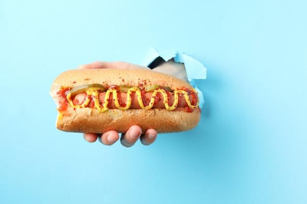 De hand houdt hotdog van gat op blauwe oppervlakte
