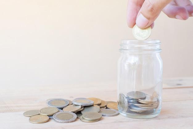 De hand houdt munt en zetten spaarmunten in glas met een stapel van coinson houten tafel - investeringen, business, finance en banking concept
