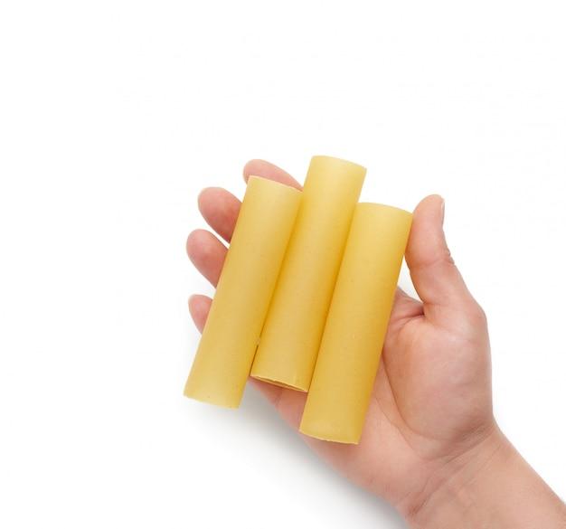 De hand houdt ruwe cannelloniendeegwaren van lichaamsdeel dat op witte achtergrond wordt geïsoleerd