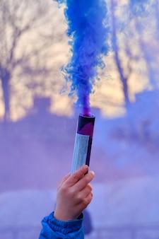 De hand houdt vuurwerk vast met een rook in de kleur blauw.