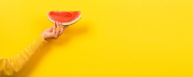 De hand houdt watermeloenplak over geel