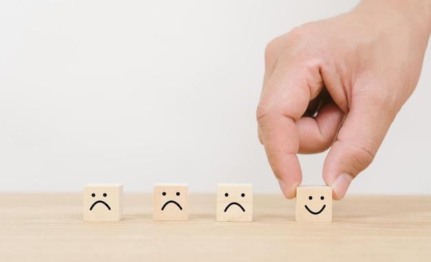 De hand kiest de groei van het smileygezicht op de houten blokkubus op witte achtergrond, het bedrijfsconcept van de beoordeling van de klantervaring