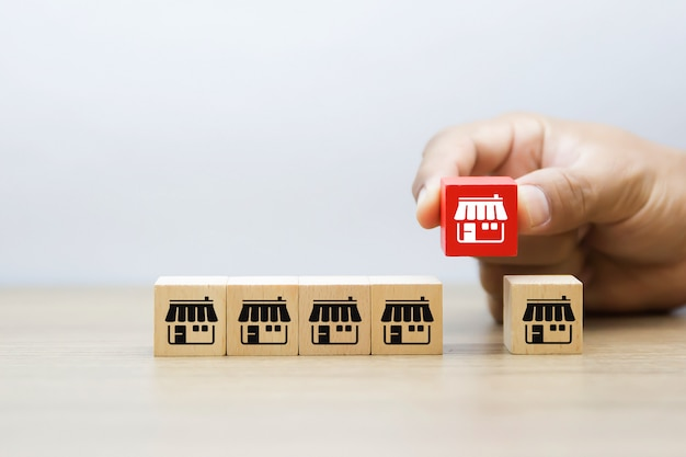 De hand kiest franchise pictogrammen store op houten blog.