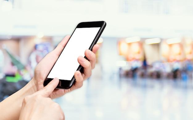 De hand klikt mobiele telefoon met onduidelijk beeldmensen reizen bij luchthaven achtergrond bokeh licht