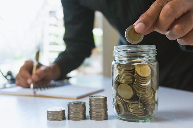 De hand laat een muntstuk met de stapel van het geldmuntstuk het groeien voor zaken vallen. financieel en boekhoudkundig concept.