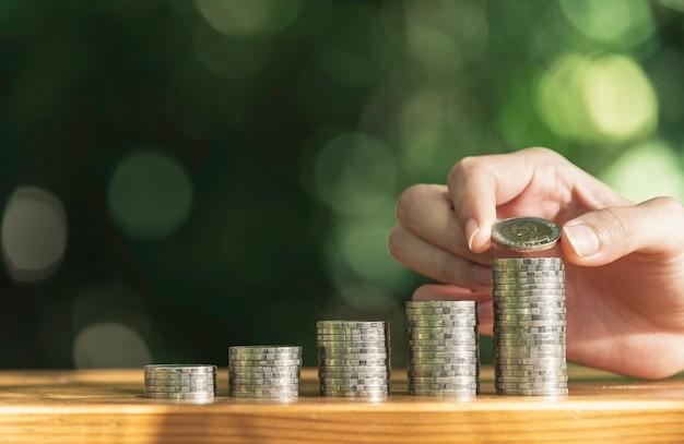 De hand laat een muntstuk met de stapel van het geldmuntstuk het groeien voor zaken vallen. financieel en boekhoudkundig
