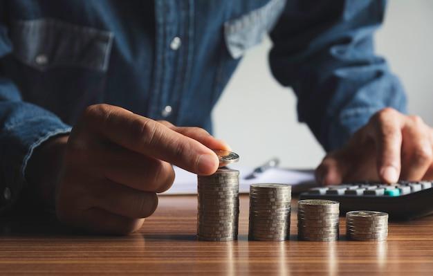 De hand laat vallen een muntstuk met de stapel van het geldmuntstuk het groeien voor zaken. financieel en boekhoudkundig concept.