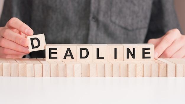 De hand legt een houten kubus met de deadline van de brief. het woord is geschreven op houten kubussen die op het witte oppervlak van de tafel staan.