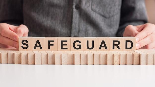 De hand legt een houten kubus met de letter safeguard. het woord is geschreven op houten kubussen die op het witte oppervlak van de tafel staan.