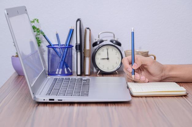 De hand maakt aantekeningen in het boek aan het bureau in de kamer