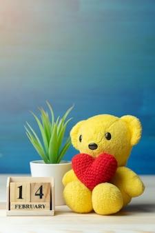 De hand maakt garen rood hart gezet op gele teddybeer naast de houten reeks van de blokkalender