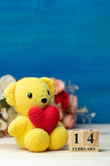 De hand maakt garen rood hart gezette op gele teddybeer naast houten blokkalender