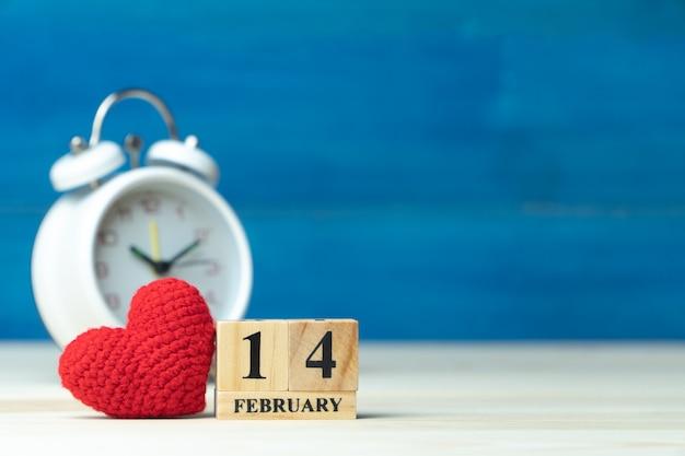 De hand maakt garen rood hart naast houten blokkalender die op valentijnskaartendatum wordt geplaatst 14 februari