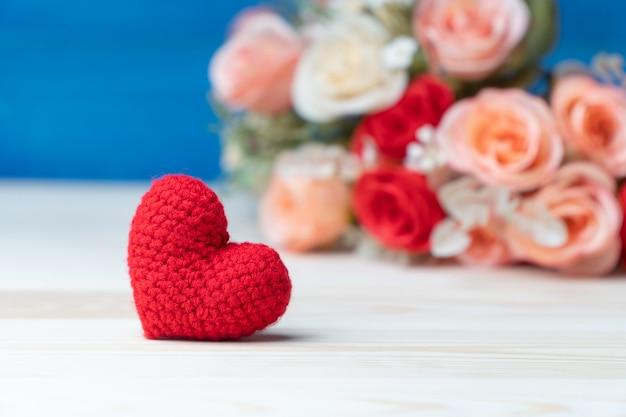 De hand maakt garen rood hart voor roze bloemboeket