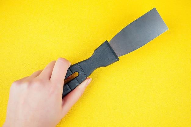 De hand met een spatel op een gele achtergrond