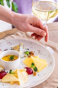 De hand neemt een glas witte wijn. kaasschotel. een bord met diverse kazen. snacks. glas wijn met kaas.