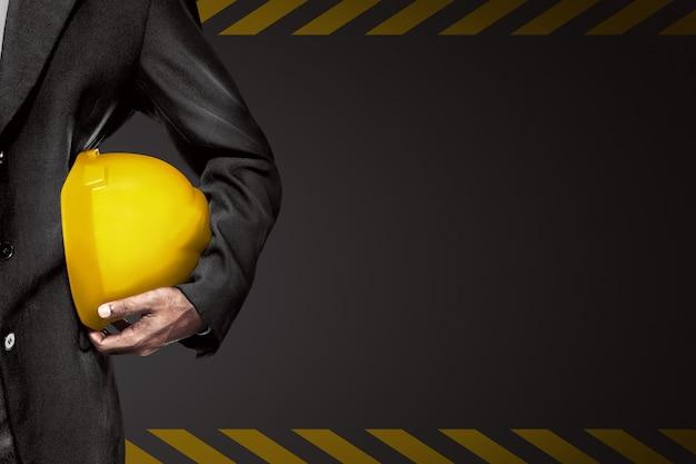 De hand of de arm van ingenieur houdt gele plastic helm voor arbeider