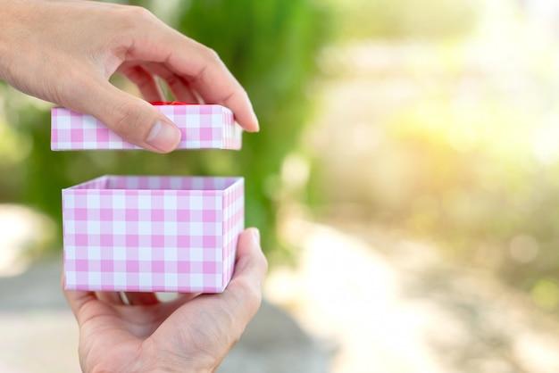 De hand opent de doos op onduidelijk beeldachtergrond met exemplaarruimte