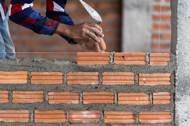 De hand professionele bouwvakker die van de close-up bakstenen in nieuwe industriële plaats legt