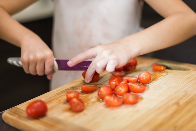 De hand scherpe tomaten van het meisje op houten hakbord met mes