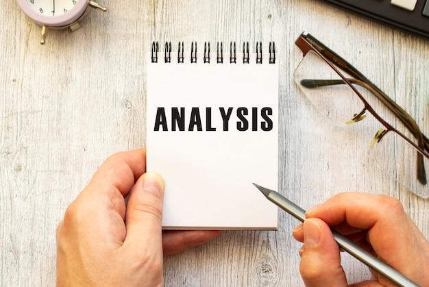 De hand schrijft de tekst analysis in potlood in een notitieboekje