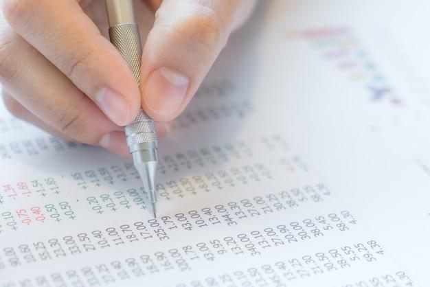 De hand schrijft op diverse financiële grafieken op de tabel