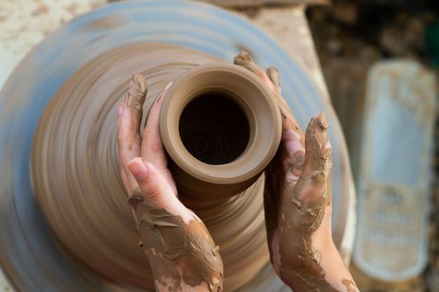 De hand sluiten van het kind dat aardewerk maakte.
