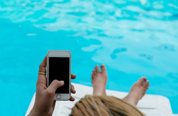 De hand speelt witte smartphone bij zwembad vrouw gebruikend haar telefoon terwijl het zitten ontspant bij p