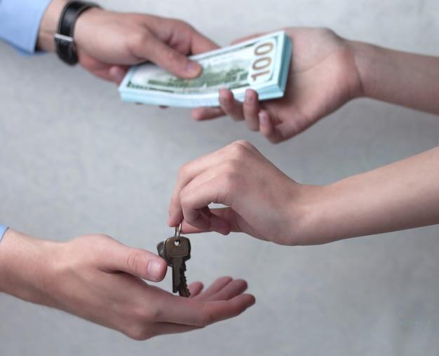 De hand stopt het geld in een doos om de accumulatie op te slaan.