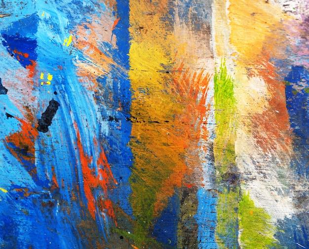 De hand trekt de kleurrijke abstracte achtergrond van het textuurolieverfschilderij op houten.