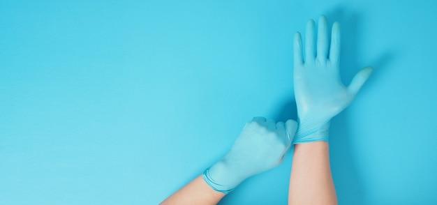 De hand trekt doktershandschoenen of blauwe latexhandschoenen van de rechterhand op een blauwe achtergrond.