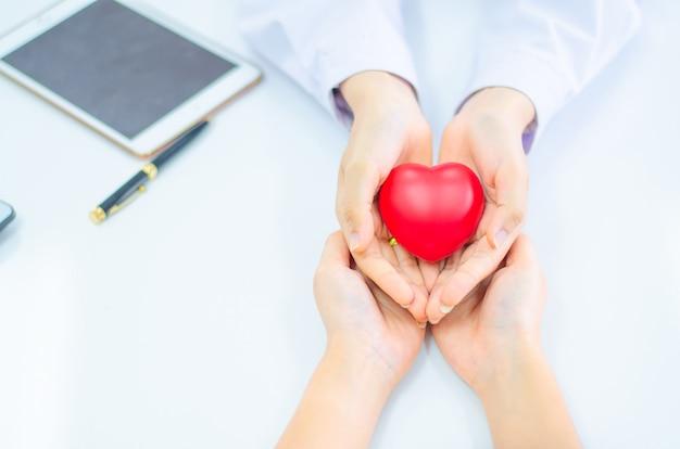 De hand van arts geeft hart aan mensenhand